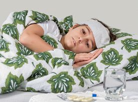 picture of high fever  - Sick boy lying in bed with high fever - JPG