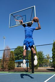 pic of slam  - Young basketball player driving to the hoop for a high flying slam dunk - JPG