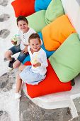 picture of brother sister  - Two cute kids brother and sister drinking fresh smoothies on a colorful pillows at outdoor cafe on summer day - JPG