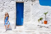 pic of greek  - Charming little girl at typical greek traditional village with white houses and colorful doors on Mykonos Island - JPG