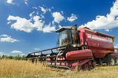 stock photo of combine  - Combine harvester at the edge of grain field during hot harvest time