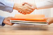 stock photo of passed out  - entrepreneur shaking hands with his accuntant after passing documenation and invoices