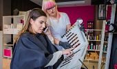 stock photo of hair dye  - Beautiful young woman looking with hairdresser a hair dye palette while talking by her smartphone - JPG