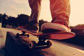 foto of skateboard  - closeup of skateboarder legs skateboarding at sunrise skatepark - JPG