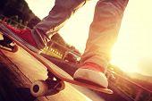 image of skateboard  - closeup of skateboarder legs skateboarding at sunrise skatepark - JPG