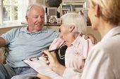 foto of retired  - Retired Senior Couple Sitting On Sofa Talking To Financial Advisor - JPG