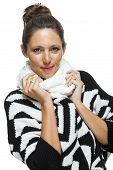 picture of snuggle  - Attractive elegant woman in winter fashion snuggling down into her white scarf and black and white jumper to ward off the cold winter weather on white - JPG