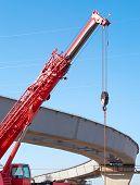 stock photo of road construction  - hoisting crane construction of overhead road - JPG