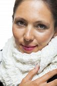 foto of snuggle  - Attractive elegant woman in winter fashion snuggling down into her white scarf and black and white jumper to ward off the cold winter weather on white - JPG