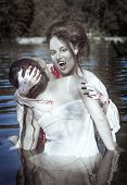 stock photo of bloody  - Beautiful vampire woman dressed white bloody shirt and her victim standing in the river - JPG