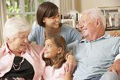image of grandparent child  - Grandparents Sitting On Sofa With Grandchildren Indoors - JPG