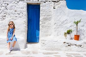 stock photo of greek-island  - Charming little girl at typical greek traditional village with white houses and colorful doors on Mykonos Island - JPG