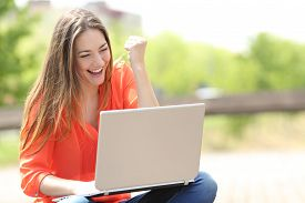 image of self-employment  - Euphoric woman searching job with a laptop in an urban park in summer - JPG