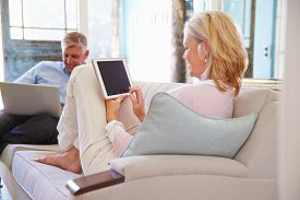 picture of maturity  - Mature Couple At Home In Lounge Using Digital Devices - JPG