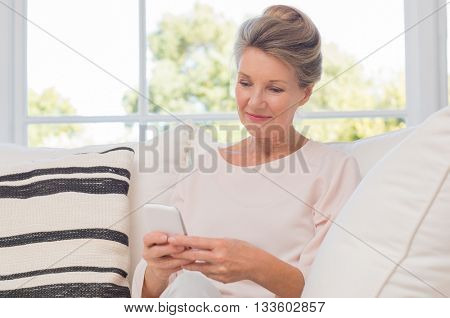 Senior woman using mobile phone while sitting on sofa. Older woman sitting on sofa and texting a pho