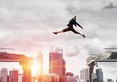 Business Woman Jumping Over Gap In Concrete Bridge As Symbol Of Overcoming Challenges. Sunlight And  poster