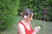 Young Woman Listening To Music With Headphones Outdoors On A Beautiful Sunny Day. Listen To Music Wi poster