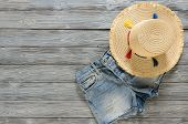 Womens Clothing, Accessories (denim Shorts, Straw Hat) On Grey Wooden Background With Copy Space. Tr poster