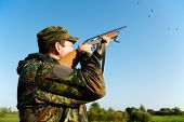stock photo of duck-hunting  - Male hunter in camouflage clothes on the field aiming and shooting with hunting rifle to gamebird during a hunt - JPG