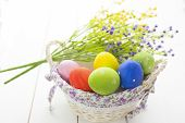 Beautiful Flowers And Easter Eggs Basket. Easter Eggs In Basket On Wooden Surface. poster