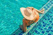 Beautiful tanned woman in swimwear relaxing in swimming pool spa. poster