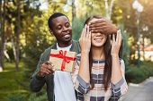 Young African-american Man With Giftbox Closing His Girlfriend Eyes To Make Surprise For Her, Walkin poster