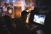 Gamer With Beard Plays Games On A Home Computer. A Young Man Sits At Home In His Room And Plays Game poster