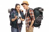 Female teenage tourist showing pictures on a camera to a male tourist isolated on white background poster