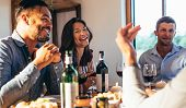 Group Of Happy Friends Enjoying Party At Home. Men And Women Sitting At Dining Table And Enjoying Me poster