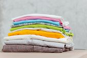 Close Up Pile Of Ironing Colorful Clothes, Washed Laundry, Family Clothing On Ironing Board Isolated poster