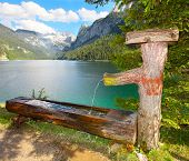 Fountain with drinking water over a Vorderer Gosausee alpine mountain lake in Salzkammergut, Austria