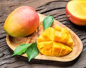 Mango fruits and mango slices on the old wooden table. poster