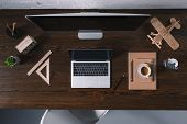 Top View Of Desktop Computer, Laptop And Office Supplies On Wooden Table poster
