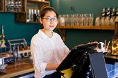 Smiling Asian Cashier Working In Cafe And Looking At Camera. Positive Confident Young Woman In Eyegl poster