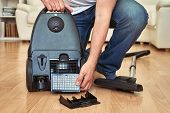 Man Replacing A Hepa Filter In Vacuum Cleaner At Home. poster