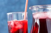 Healthy Refreshing Drink From Ice Hibiscus Tea And Red Berries And Fruits Juice In Pitcher And Tall  poster