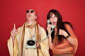 stock photo of swami  - Shocked Caucasian on phone call while bald monk points index finger upward toward heaven - JPG