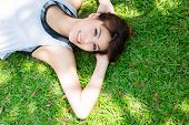 Portrait Charming Beautiful Woman. Pretty Asian Girl Lay Down On Garden In Summer Season. Attractive poster