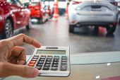 Asian Man Pressing Calculator For Business Finance On Car Showroom Blurry Background.for Automotive  poster