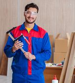 Young repairman carpenter working with clamps poster