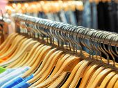 Many Of Wooden Clothes Hanger On Closet Or Clothing Rack In Shop For Sale. Fashionable Clothes In A  poster