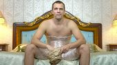 A Man With Plastic Wrap, To Lose Weight On His Hips And Stomach, Sits On The Bed And Eats Fast Food, poster