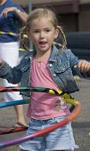 picture of hula hoop  - Smiling 4 year old blond girl hula hooping with two hoops at once outdoors - JPG