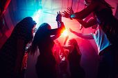 Until Sunrise. A Crowd Of People In Silhouette Raises Their Hands On Dancefloor On Neon Light Backgr poster