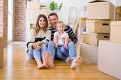 Beautiful family sitting on the floor playing with his kid at new home around cardboard boxes poster