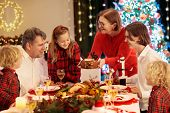 Family With Children Eating Turkey Christmas Dinner At Fireplace And Decorated Xmas Tree. Parents, G poster