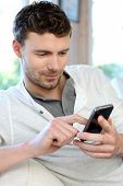 foto of man  - Young man using mobile phone to send short message - JPG