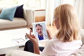 Mature Woman Having Online Consultation With Doctor At Home On Digital Tablet poster