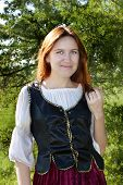 image of shepherdess  - Young medieval woman standing near the fir - JPG