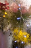Flowers And Light Garlands Behind The Wet Glass. Moist Window. Water Drops On The Glass. Blurred Lig poster